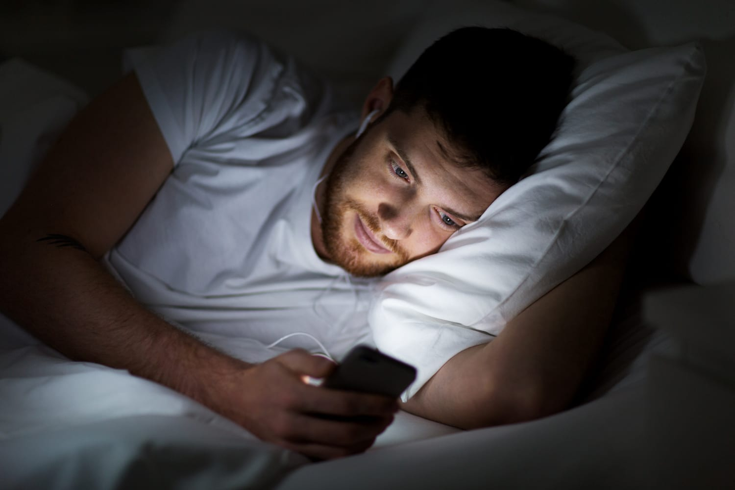 man in bed looking at his phone