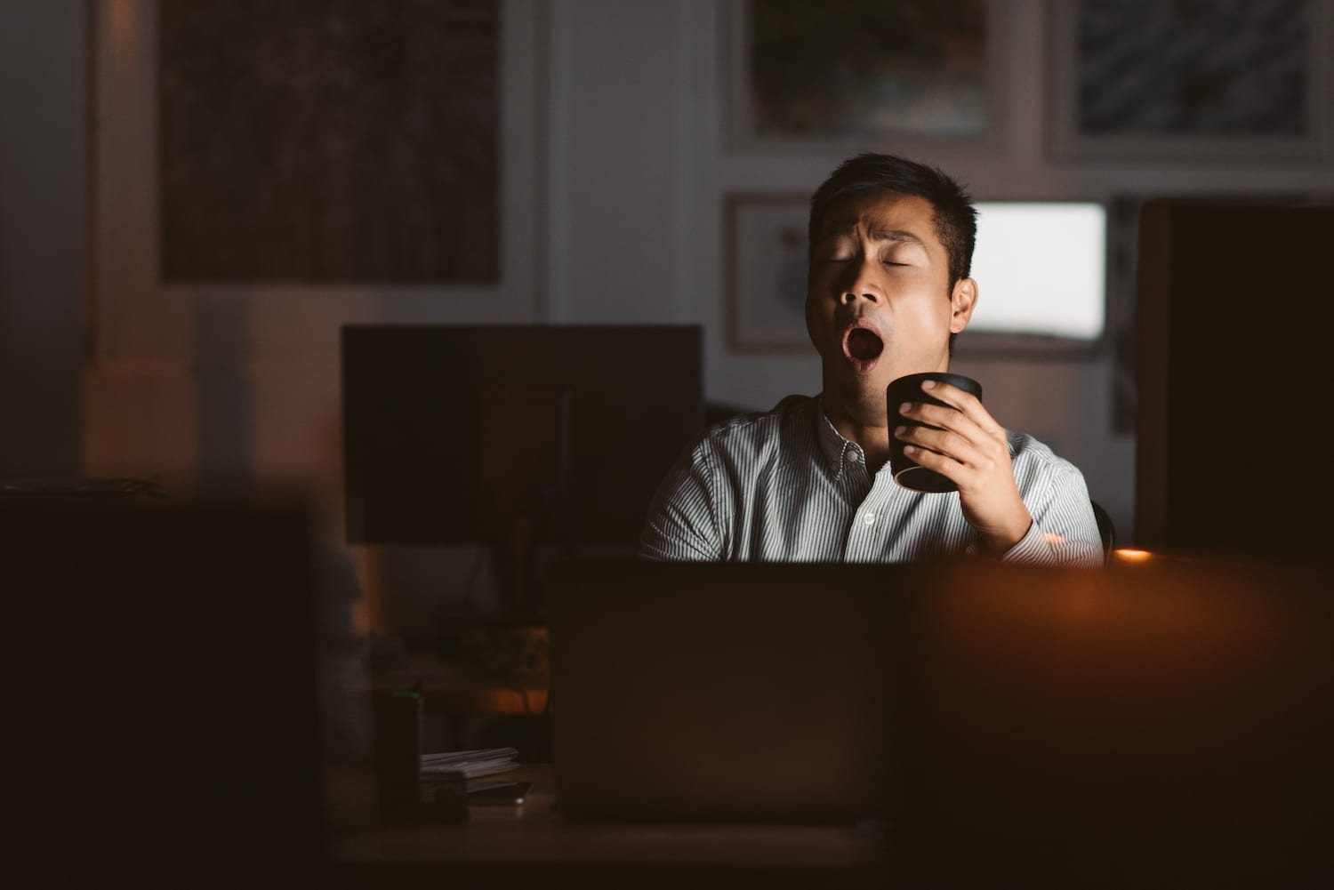 man with cup of coffee at a desk