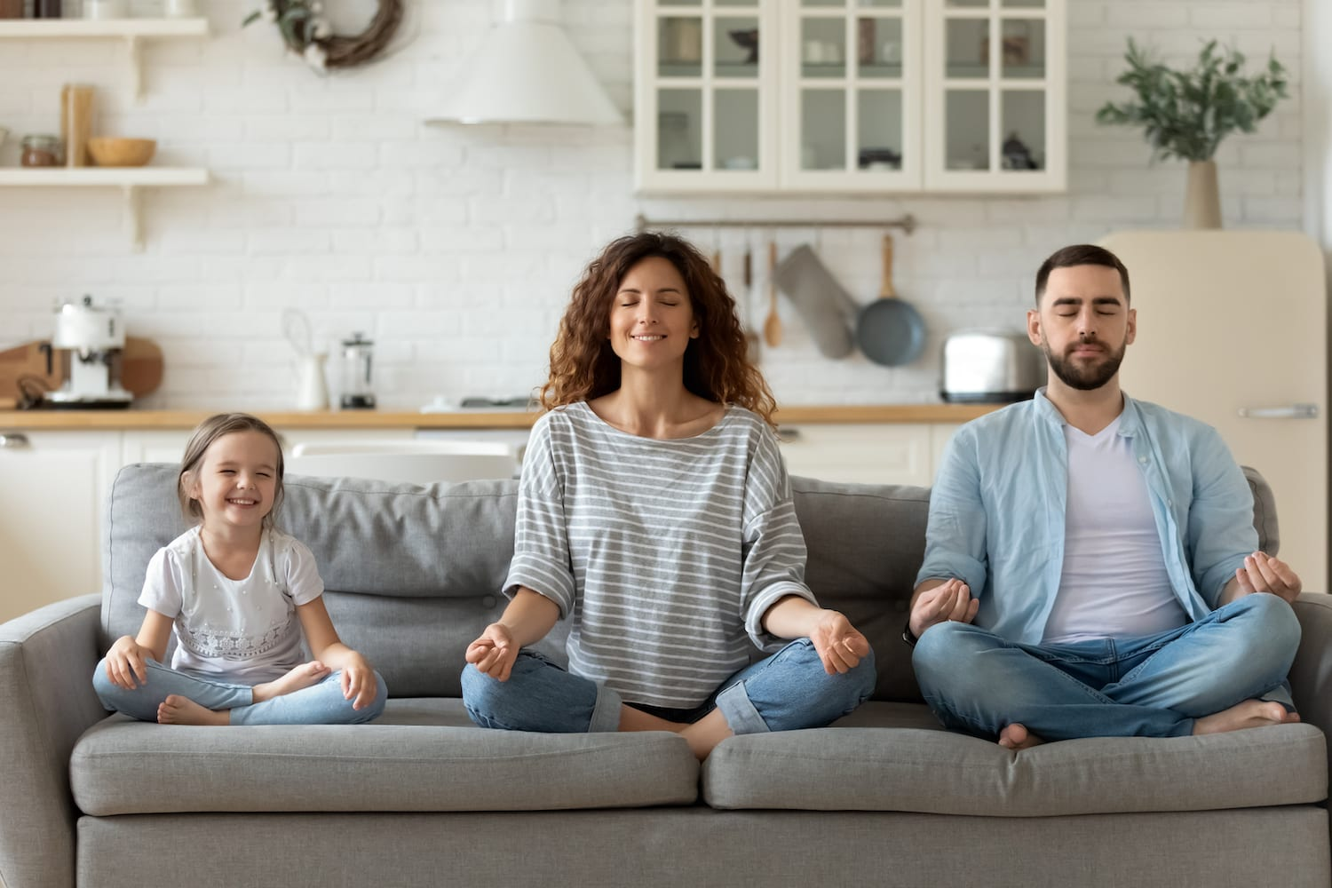 family meditating on a couch