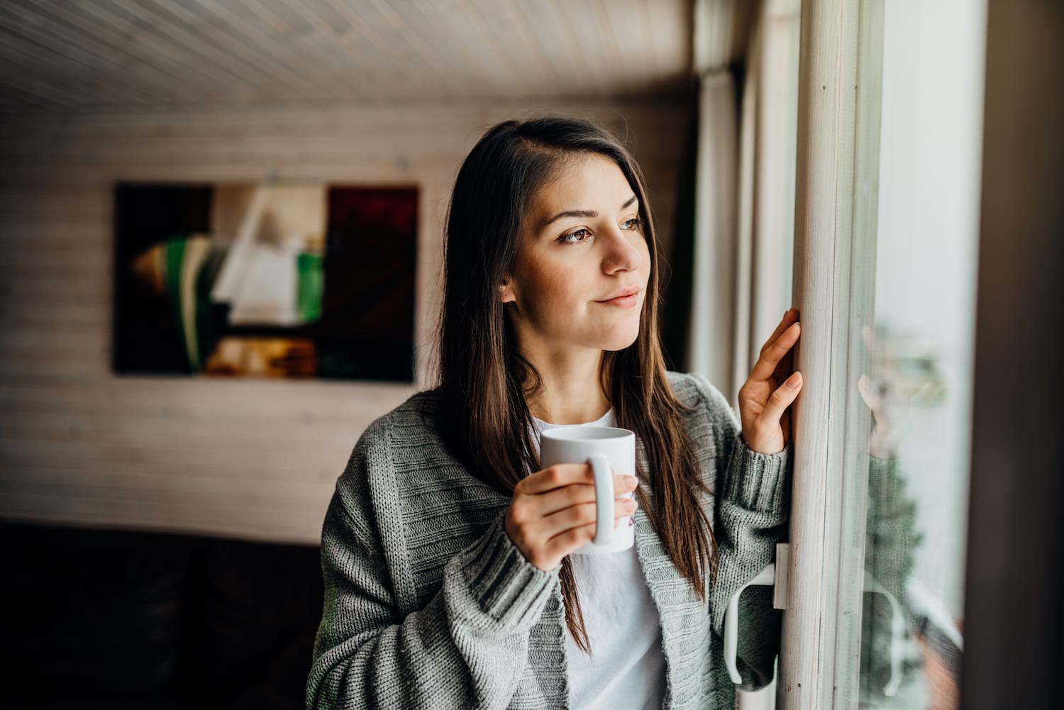woman looking out window with cup of coffee