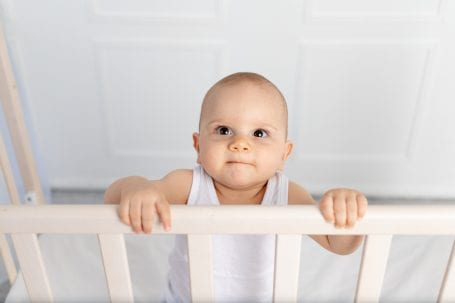 portrait of a smiling baby boy 8 months old standing in a crib