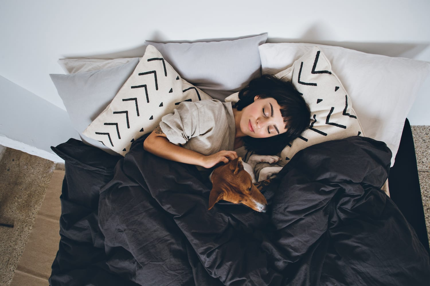 women sleeping in bed with dog