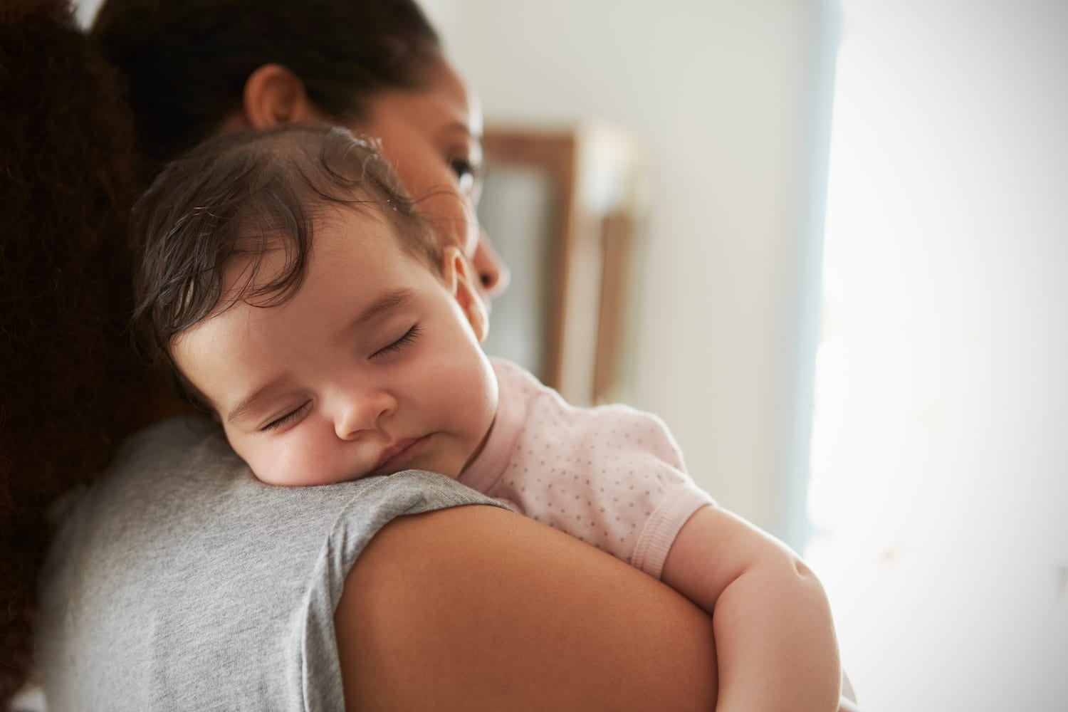 woman holding sleeping baby
