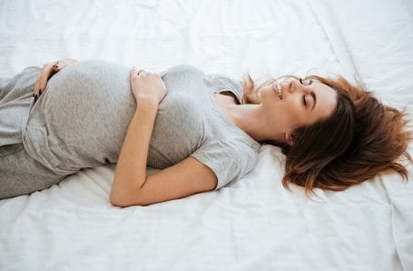 pregnant woman laying in bed smiling