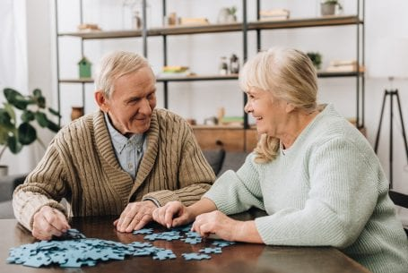 Elderly couple at table working on a puzzle
