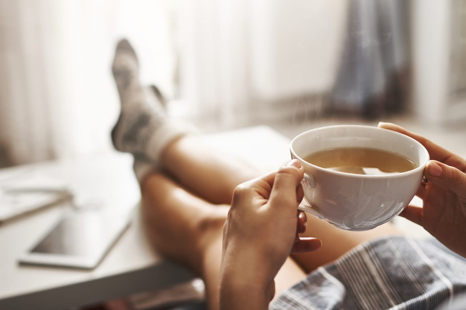 person sitting at desk with cup of coffee