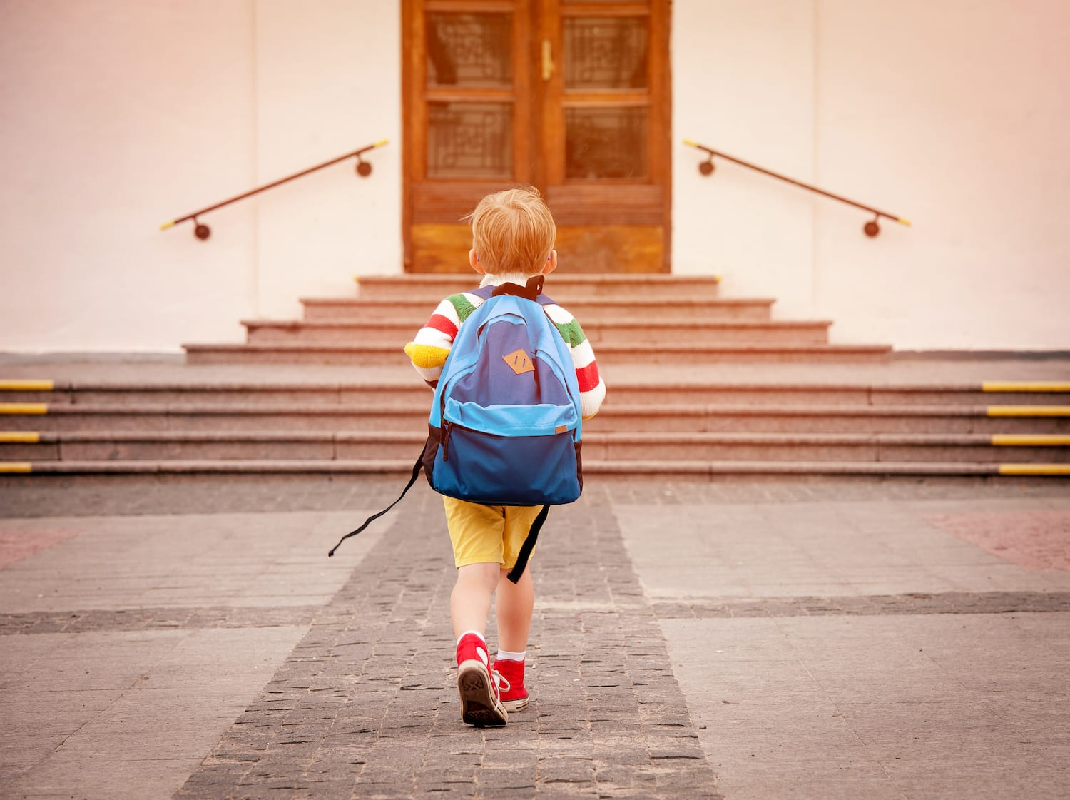 kid walking up to school with bakpack on