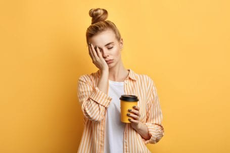 woman looking tired, holding a cup of coffee