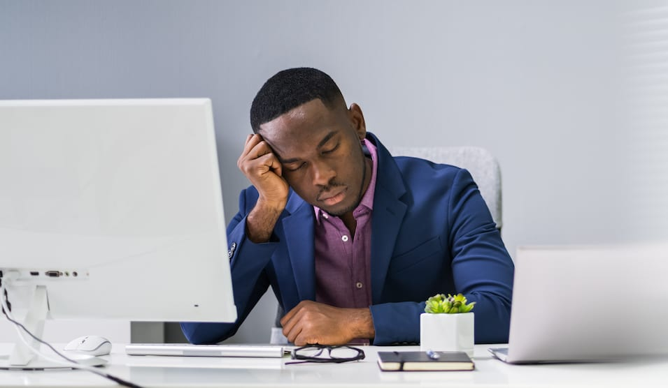 man falling asleep at his desk