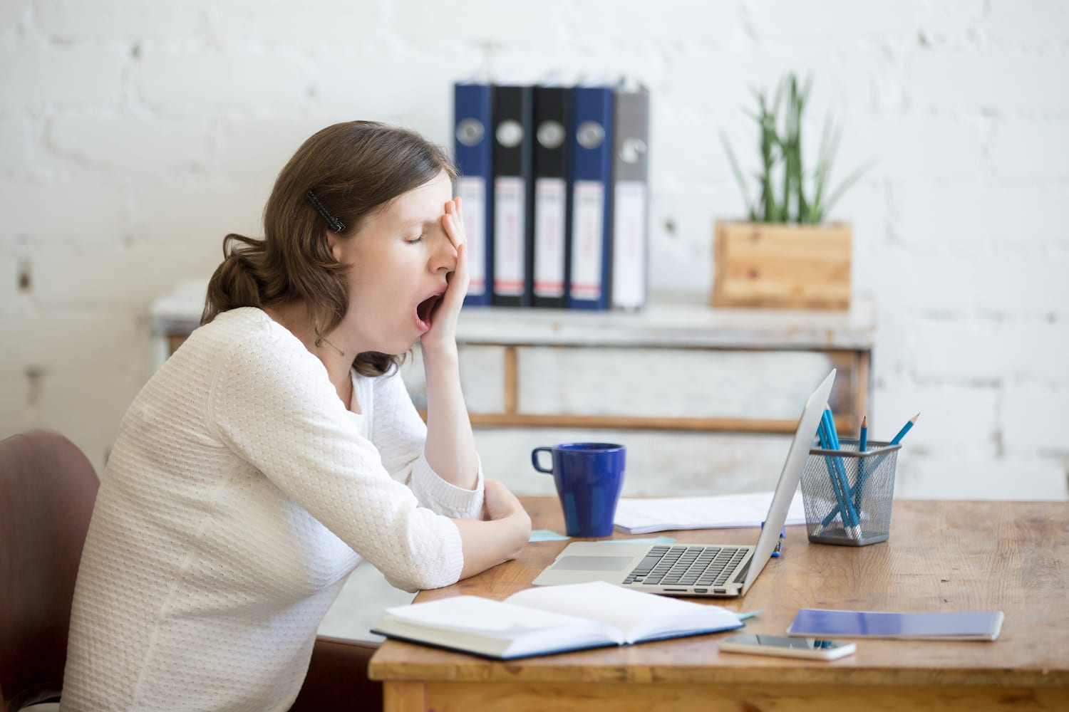 woman at desk yawning