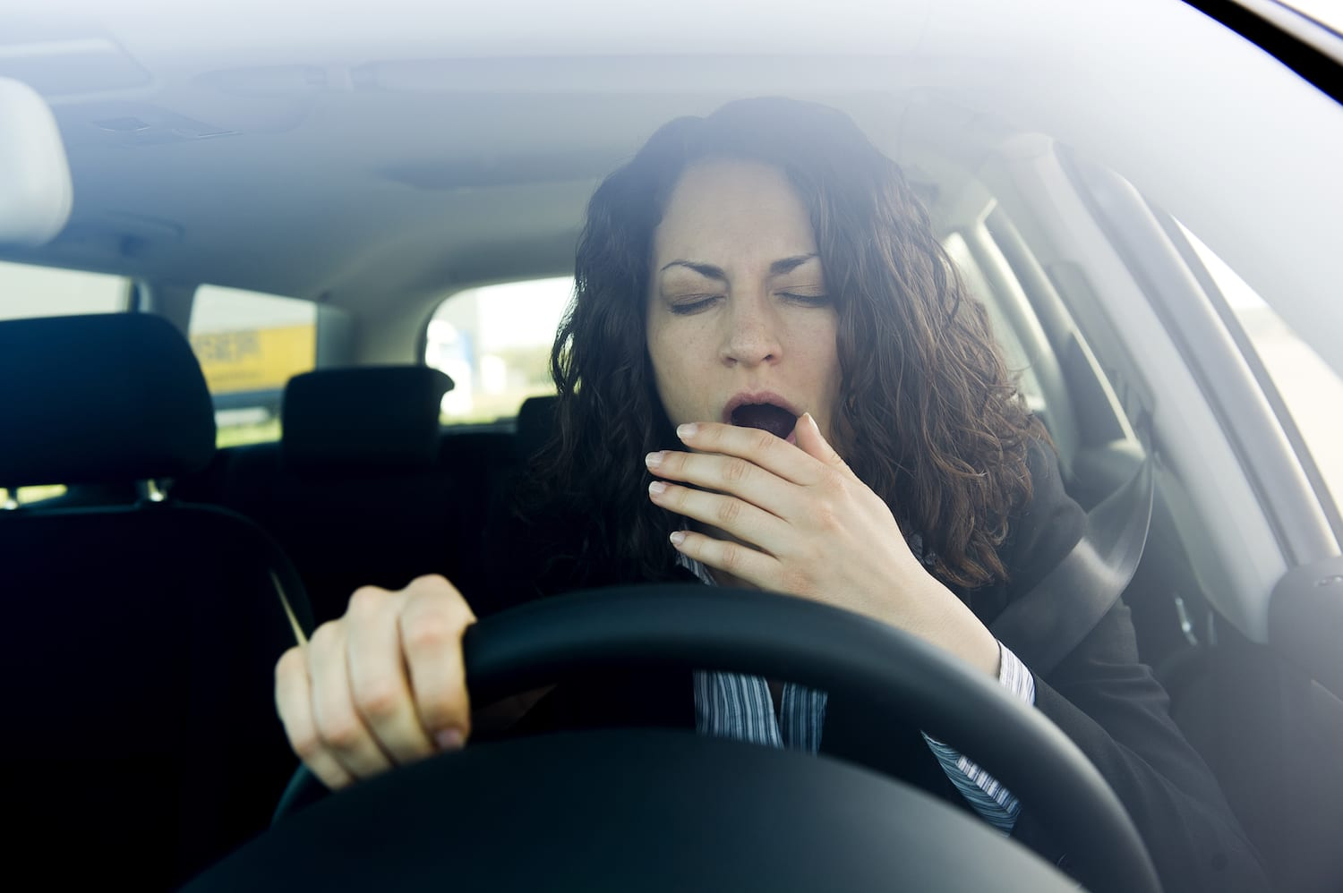 woman yawning while driving car