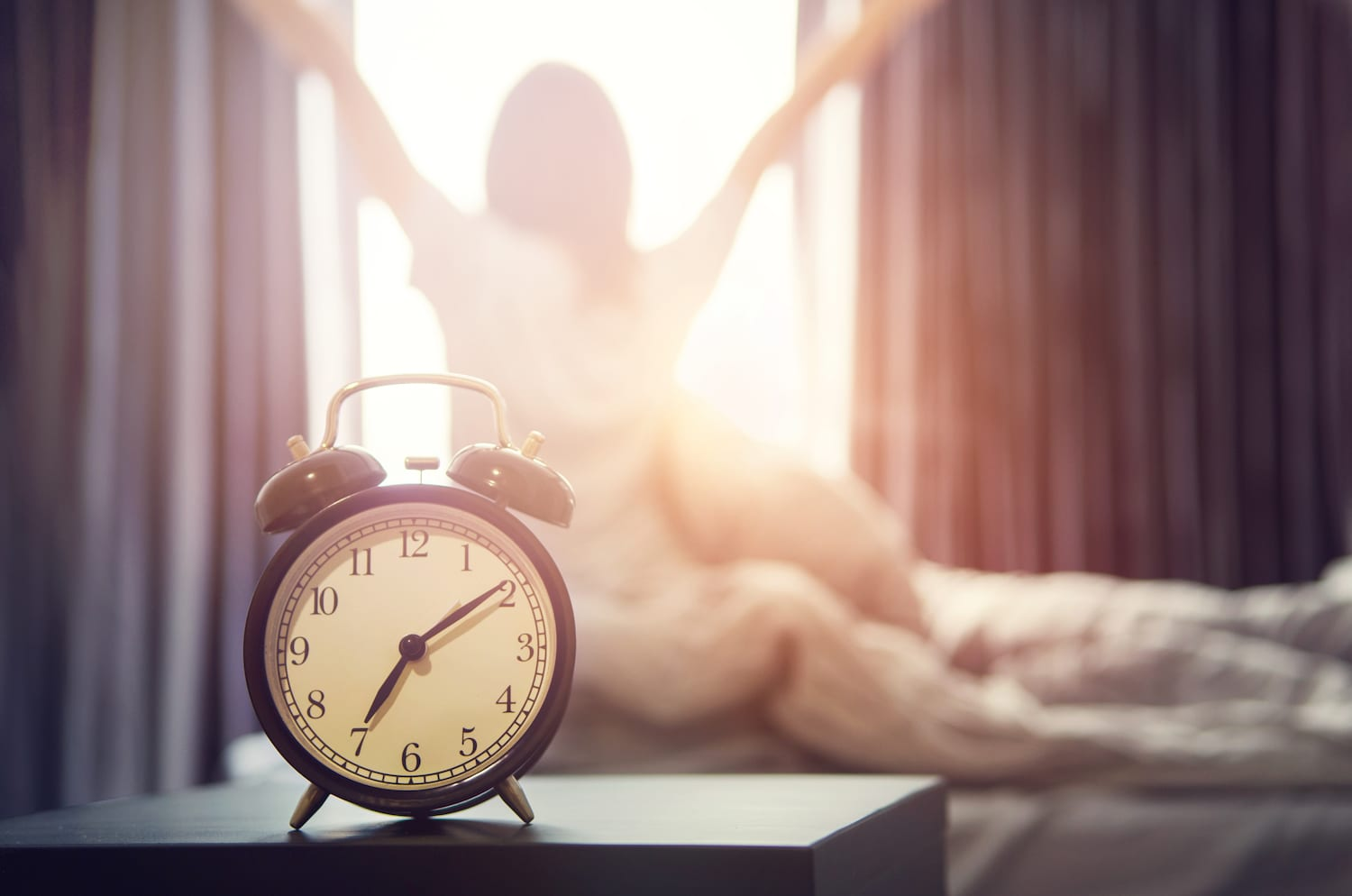 Close up of alarm clock with woman stretching in background during a sunny morning