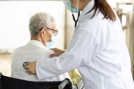 Doctor with a stethoscope on a patient's back, listening for breaths