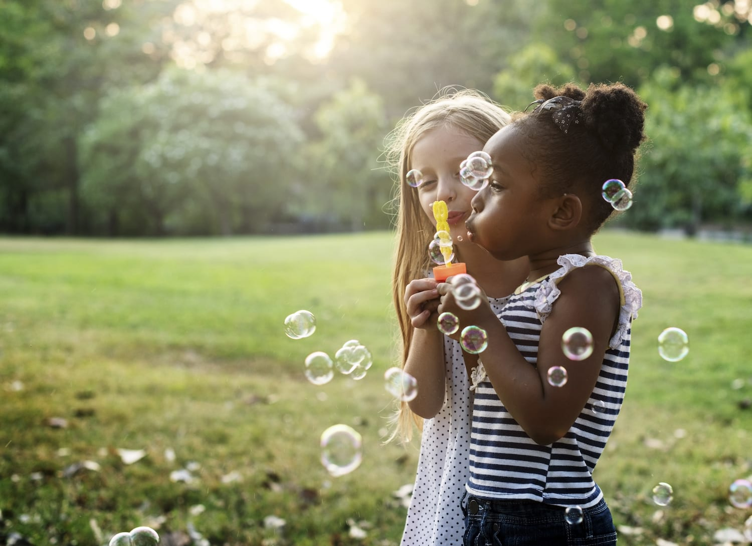 Children playing outside with bubbles