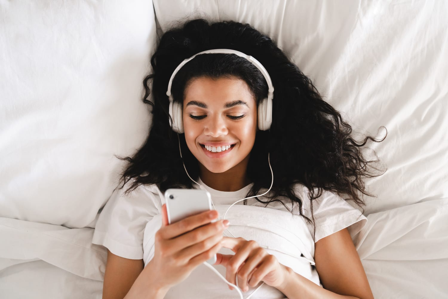 Woman in bed with headphones