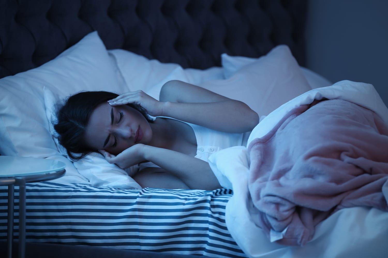 Woman awake with a nighttime headache