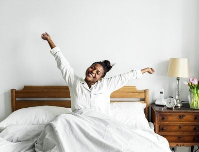 Woman waking up well-rested and stretching