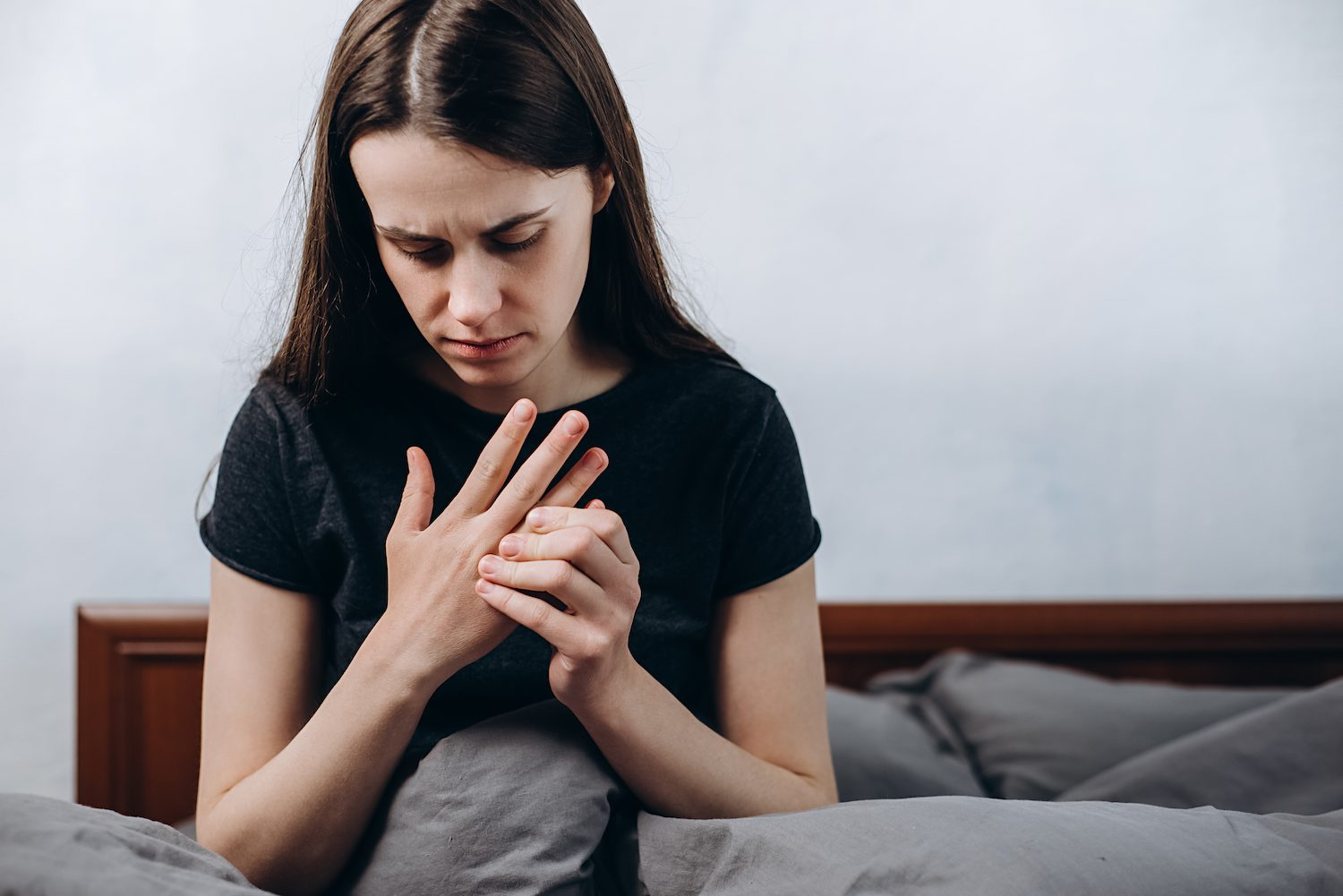 Woman holding numb hand in pain
