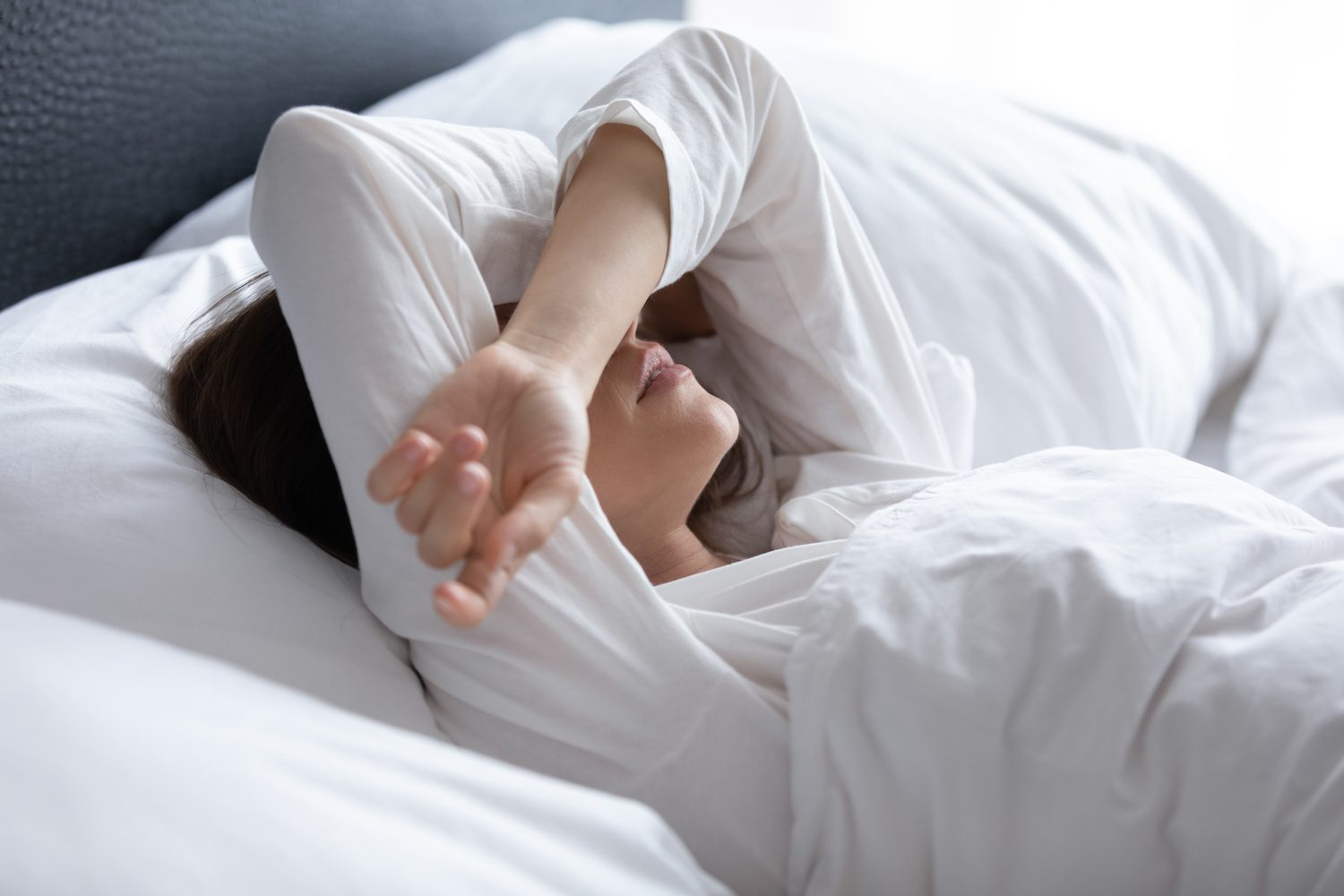 Woman waking up after bad dream, covering eyes