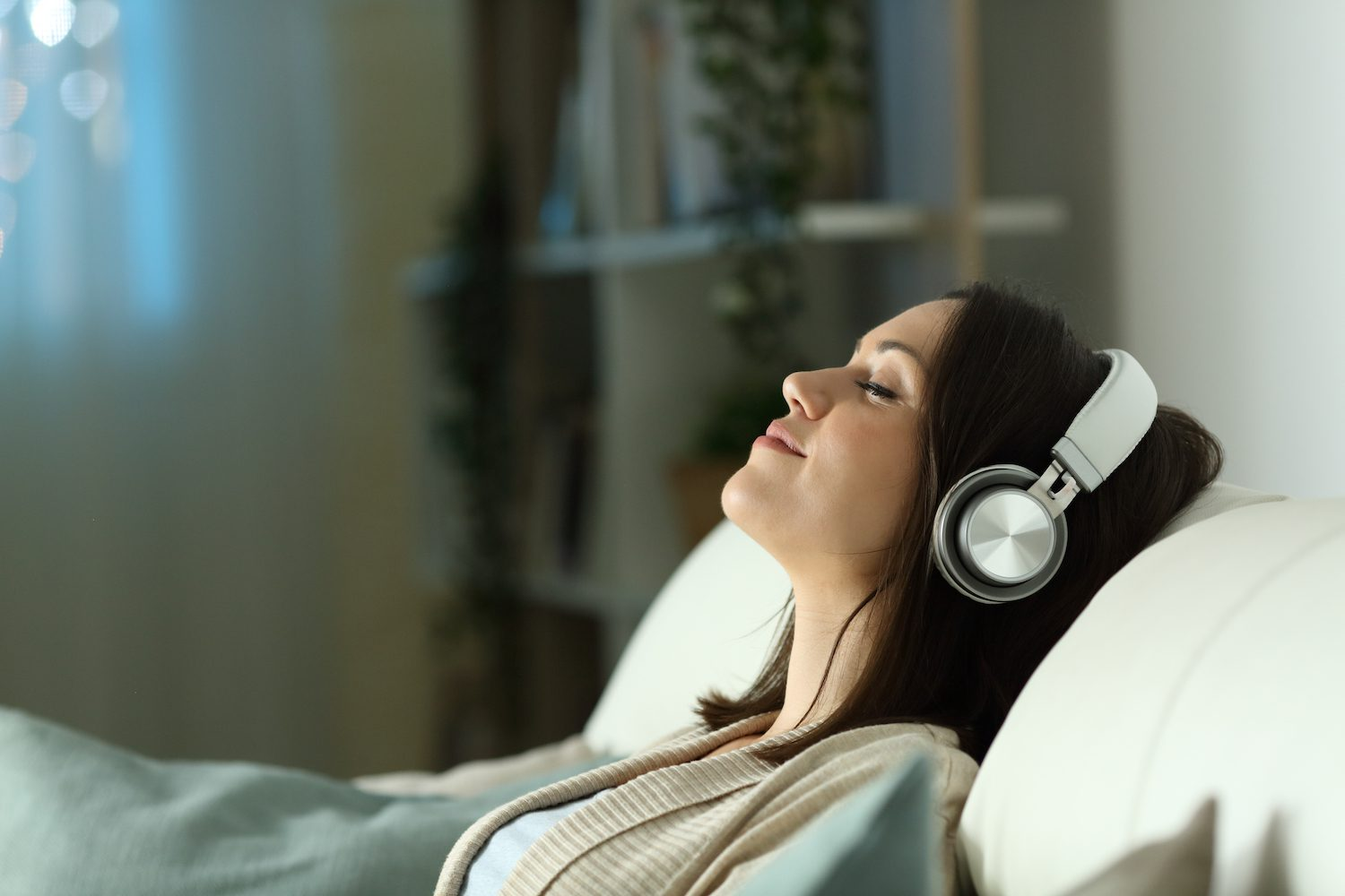 Woman listening to guided meditation before sleep