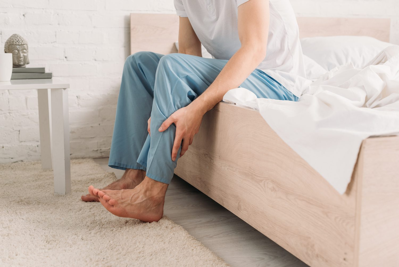 Man holding leg in pain