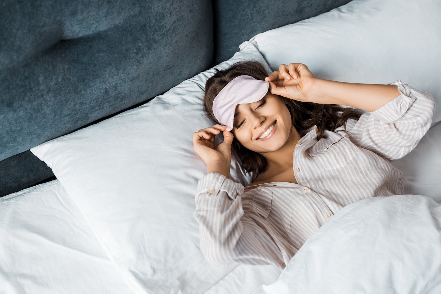 Woman waking up well rested after going to bed early