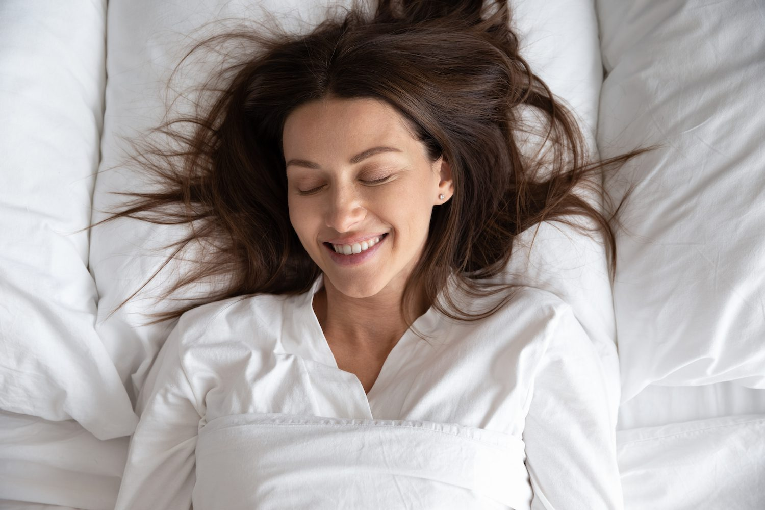Woman lying on back in bed happy