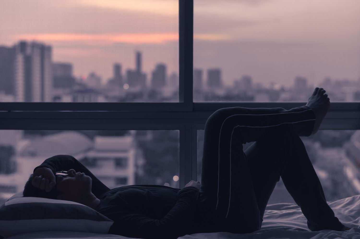 Man awake in an urban environment during the early hours of the morning