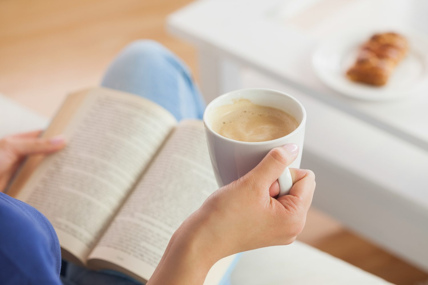 Woman holding a coffee cup while reading